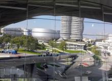 Spiegelung des BMW-Vierzylinders-Hochhauses in den Fenstern der BMW-Welt in München.