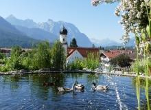 Der schönste Platz in Wallgau, die Bank am Teich. Im Hintergrund die Pfarrkirche St. Jakob und das Karwendelgebirge