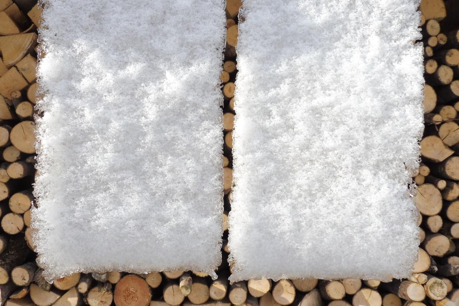 Herabfließender Schnee vor Brennholz
