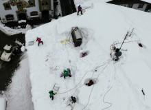Schneemassen in Wallgau, Hilfskräfte der Feuerwehr, Bergwacht, THW und Bergführer der Polizei befreien vom Statiker ausgewählte Hausdächer von der Schneelast. Bild aufgenommen von der Drehleiter der Feuerwehr.
